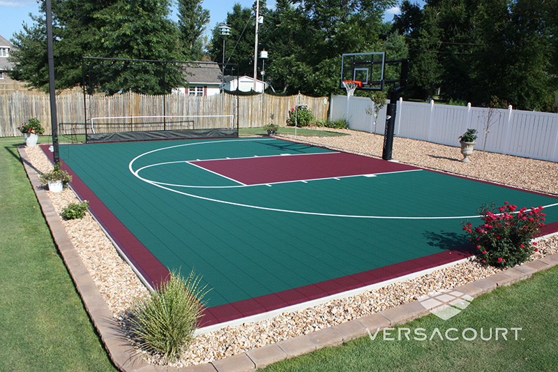 neatly landscaped backyard basketball court in burgundy and hunter green