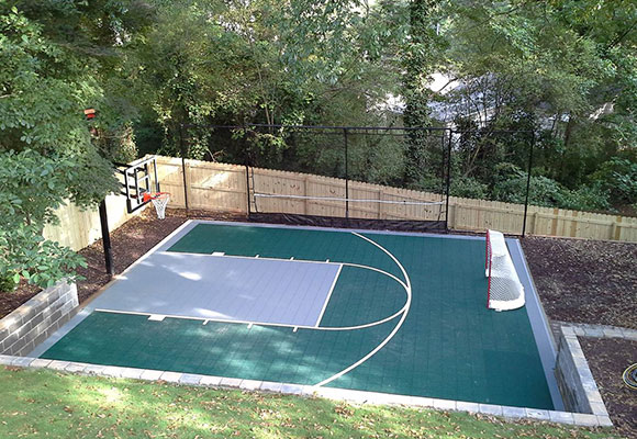 game court with basketball goal and hockey net built into backyard