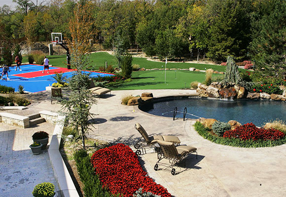 basketball court built into landscaped space with pool, patio, plants