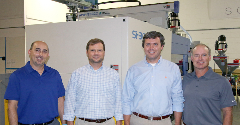 Team at the Dalton, Georgia manufacturing plant pose in front of new, state-of-the-art injection molding press