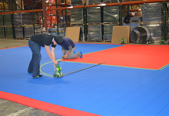 professionals pre-painting court lines on tiles in warehouse